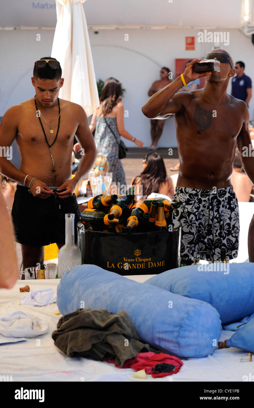 British party revelers next to large  bucket full of dozens of empty bottles of Vueve Clicquot Champagne after spraying Stock Photo