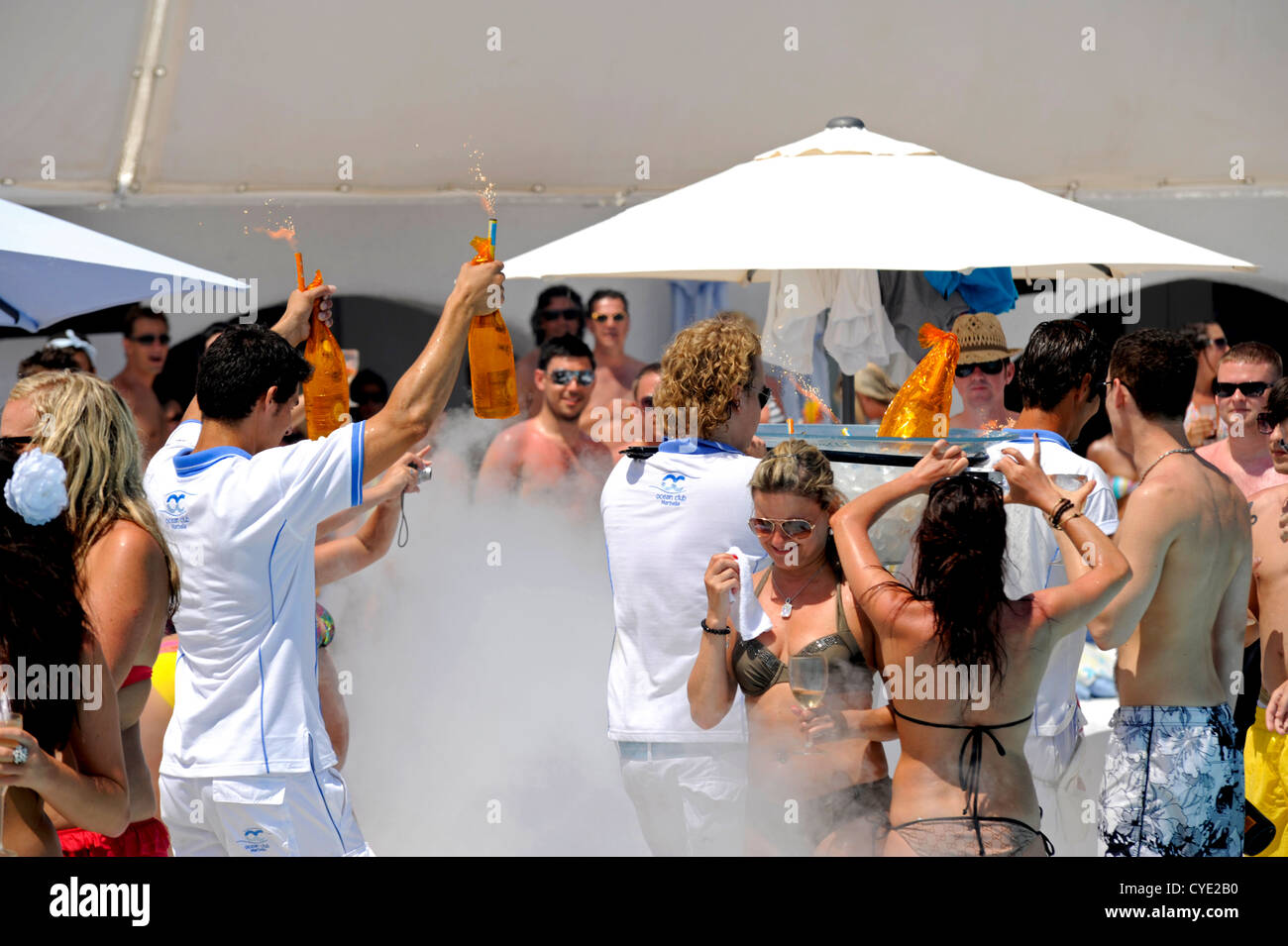 Waiters carrying bottles of Crystal champagne to a client at a pool party in Marbella - Stock Image