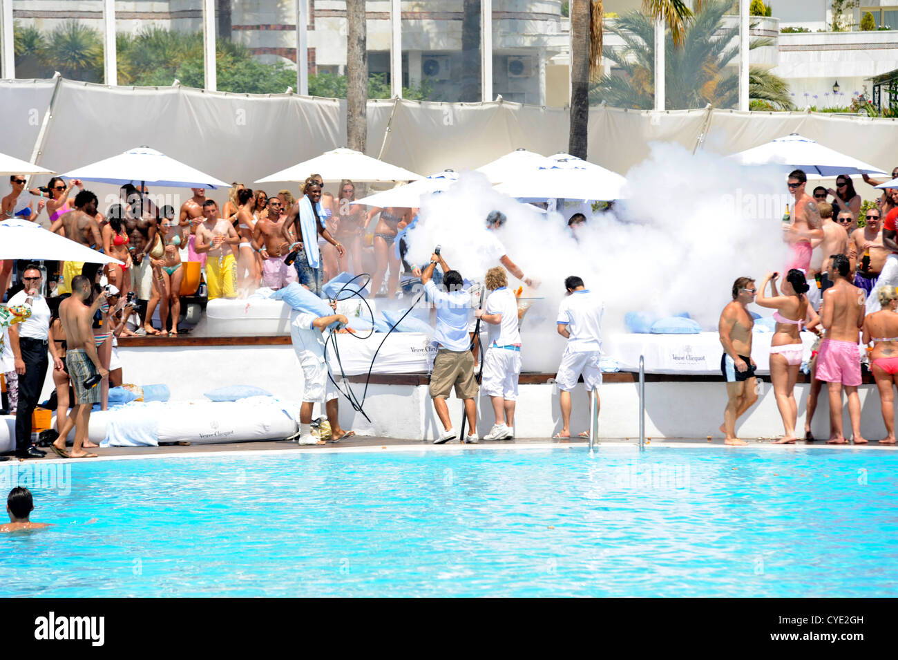 Waiters delivering large bottles of champagne to clients sun beds  at pool party, with lots of white smoke being - Stock Image