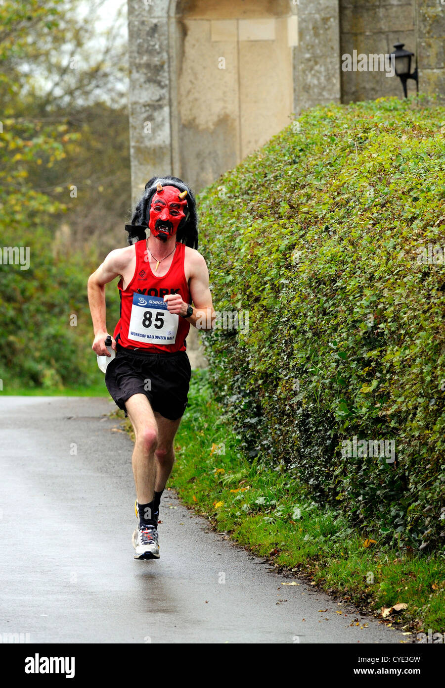 Male marathon runner wearing a red devils mask during the Worksop Halloween half marathon through Clumber Park, - Stock Image