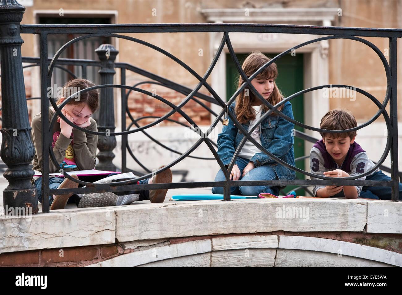 Venice, Italy. Three Italian schoolchildren on a bridge over a canal - Stock Image