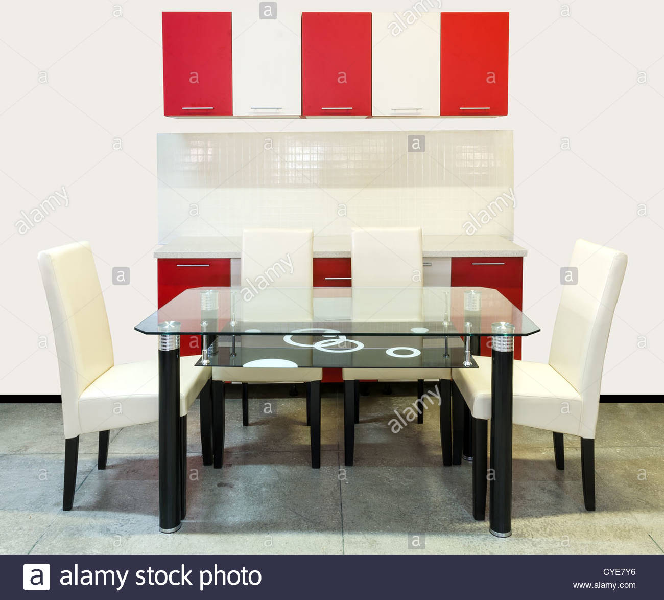 Modern kitchen furniture with wooden cupboards, glass table and tapestry chairs - Stock Image