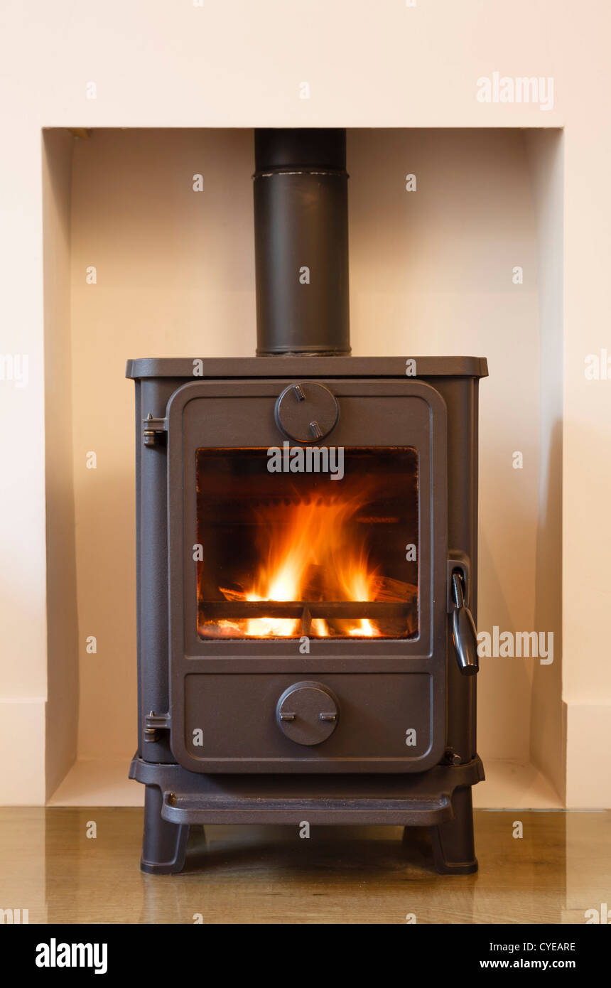 Cast iron wood burning stove in a modern contemporary fireplace - Stock Image