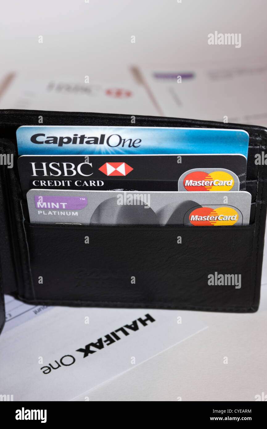 Wallet containing credit cards surrounded by credit card statements - Stock Image