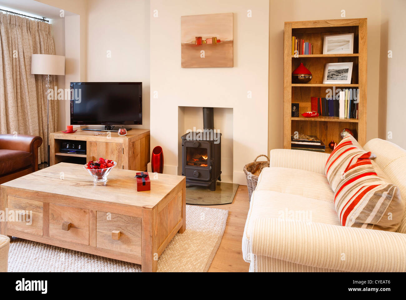 Contemporary Living Room With Neutral Colors, Wood Burner And Wooden Floor.  Photographers Own Artwork On Wall And Bookcase.