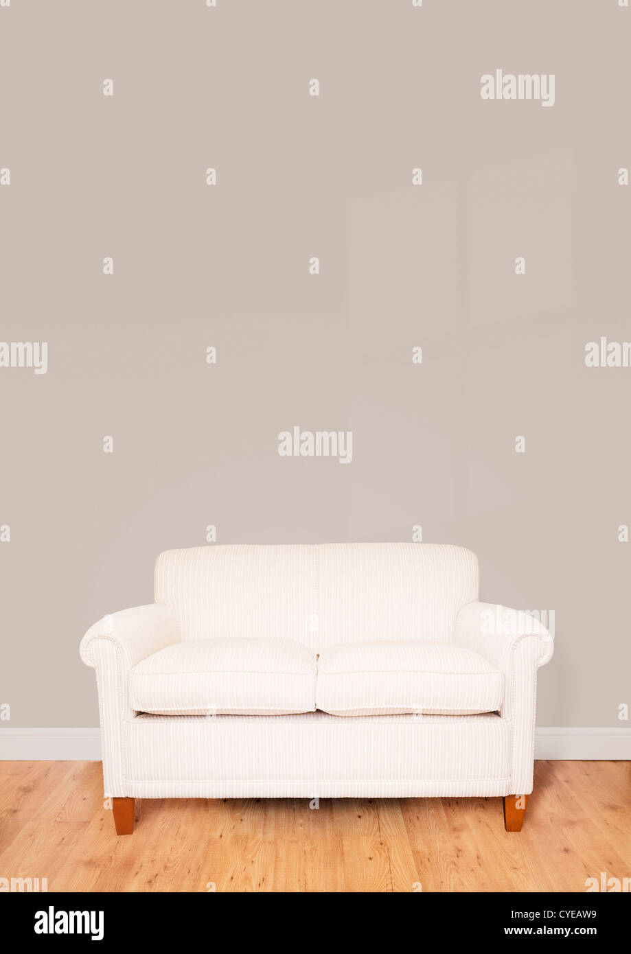 Modern cream sofa against a blank wall with lots of space for text - Stock Image