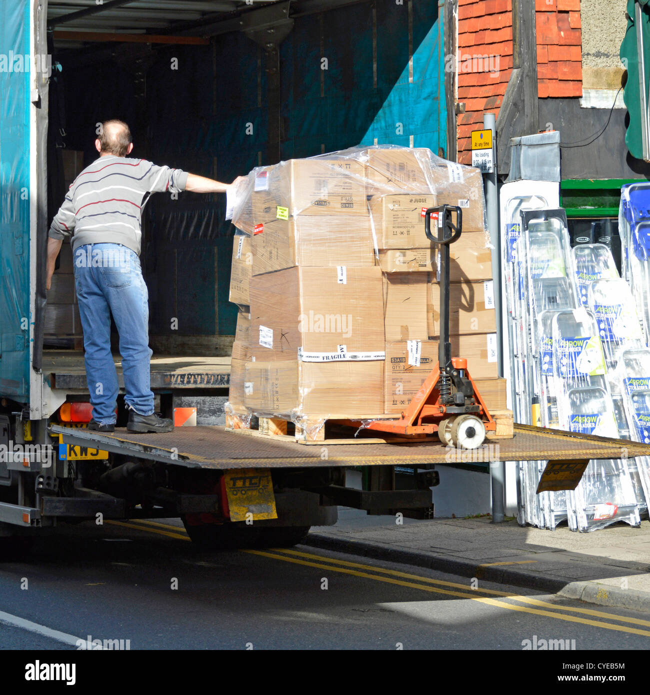 Lorry making a merchandise supplier delivery outside a High Street shop lowering to pavement using tailgate lift - Stock Image