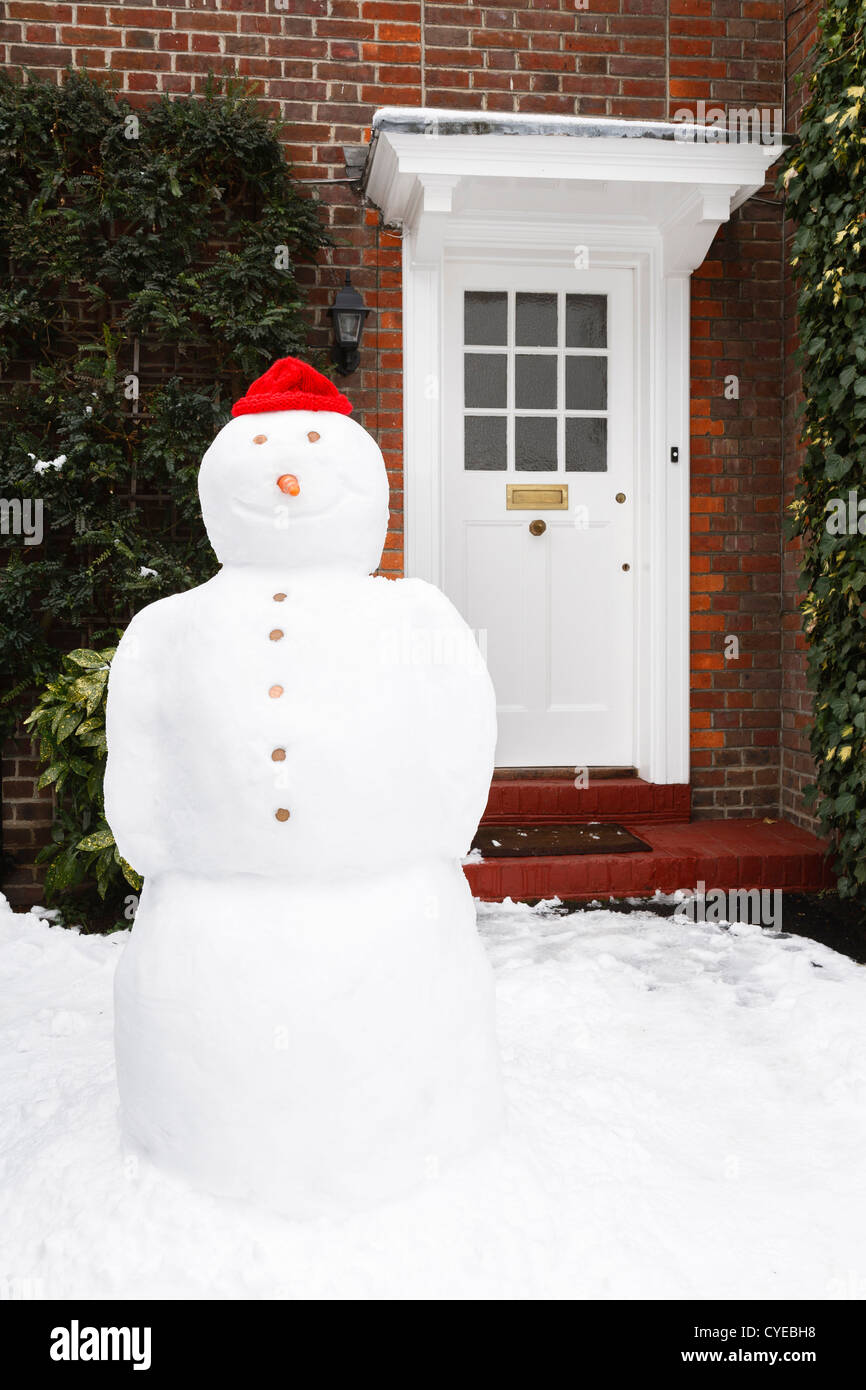 Real snowman with smile outside front door of house - Stock Image