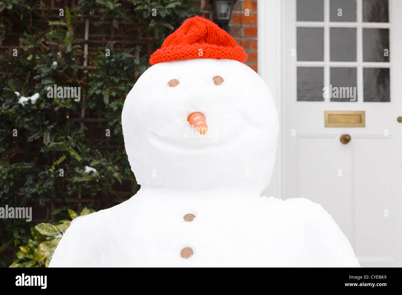 Close up of snowman with red hat and smile - Stock Image