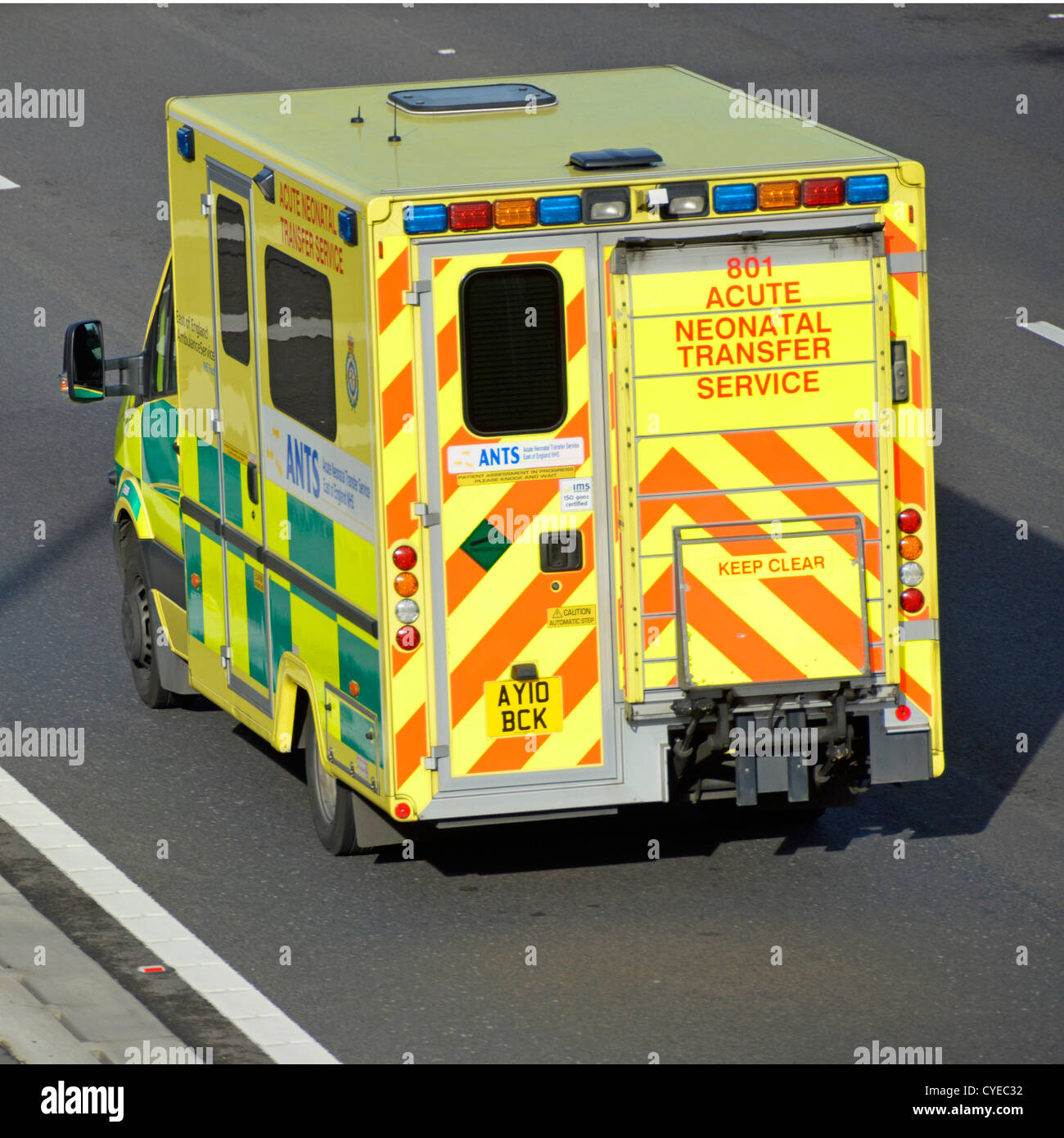 Back view of drop down tailgate loading ramp on Acute Neonatal NHS ambulance driving along M25 motorway Essex England - Stock Image