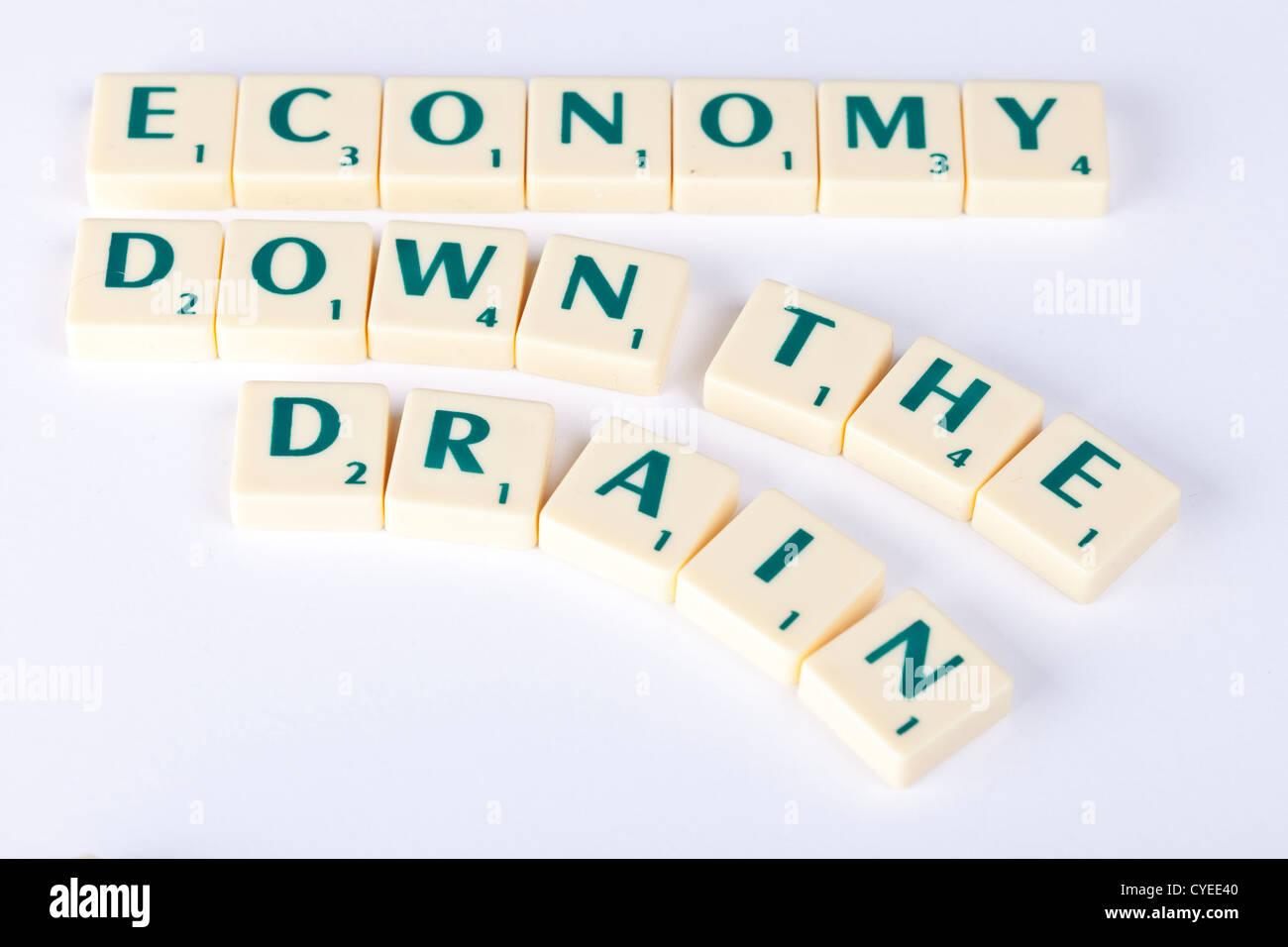 economic downturn, economy down the drain, concept illustration using scrabble letter tiles. - Stock Image