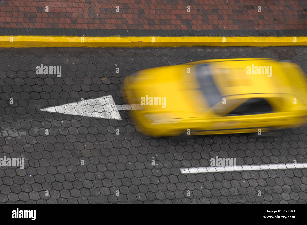 A High angle shot of a taxicab driving down a cobblestone street in Quito Ecuador - Stock Image