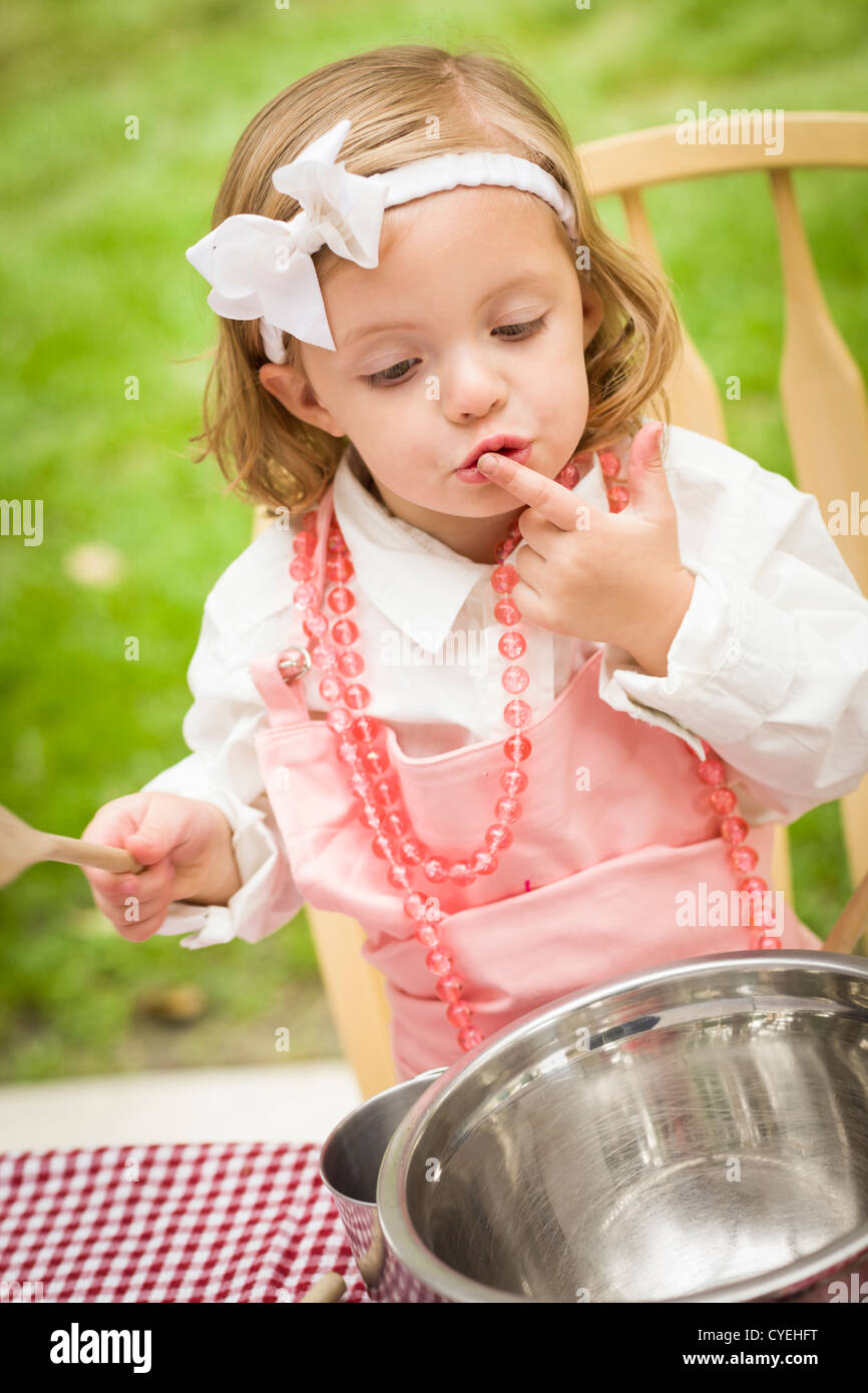 Happy Adorable Little Girl Playing Chef Cooking in Her Pink Outfit. - Stock Image