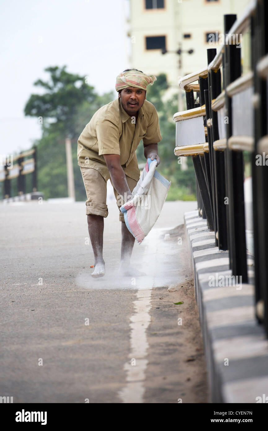 Municipal worker spreads calcium hypochlorite. Government worker spreading bleaching powder by hand on the streets - Stock Image
