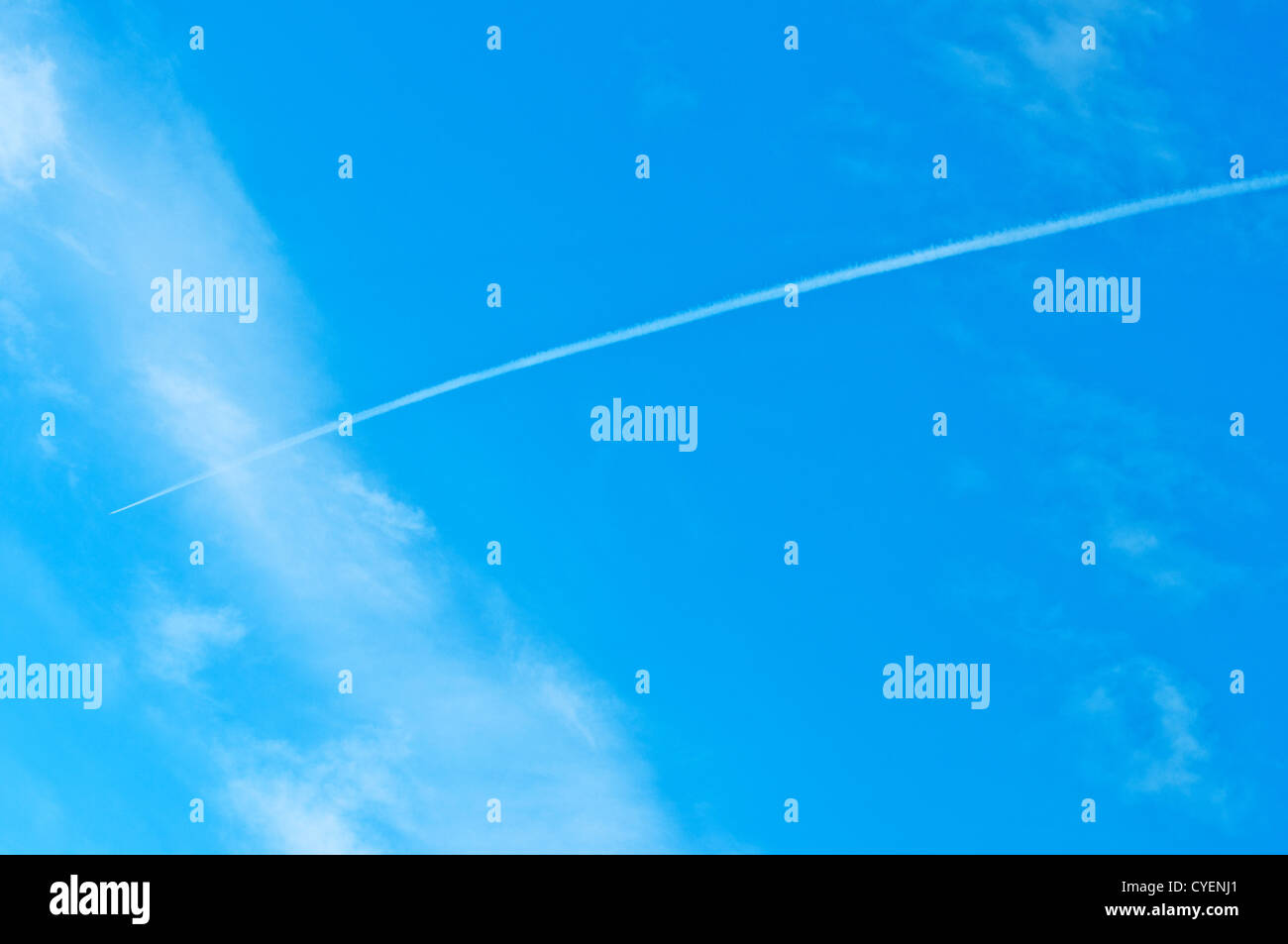 Trace of an airoplane on a cloudy blue sky - Stock Image