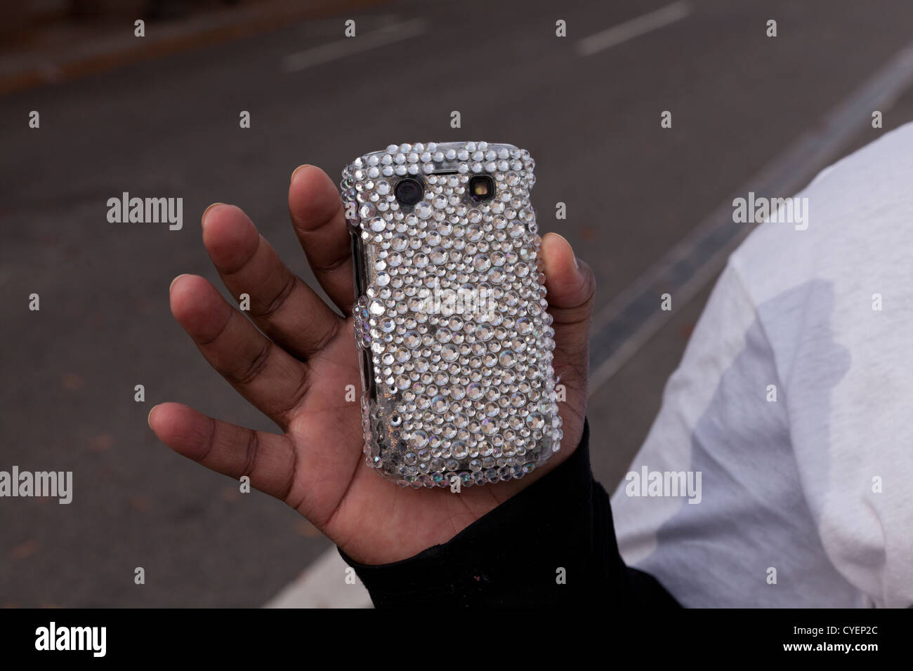 Woman holding cellphone lined with acrylic beads - Stock Image