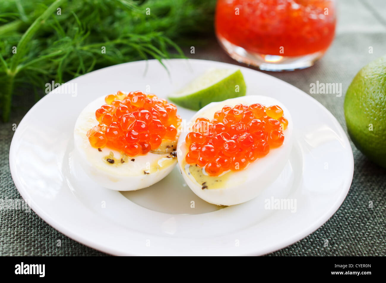 Eggs and caviar on white dish close up - Stock Image