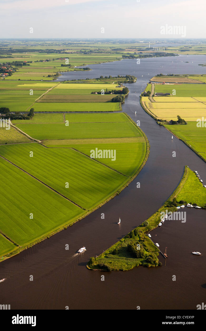 The Netherlands, near Uitwellingerga, Aerial. Farmland and boats anchored at little island. - Stock Image