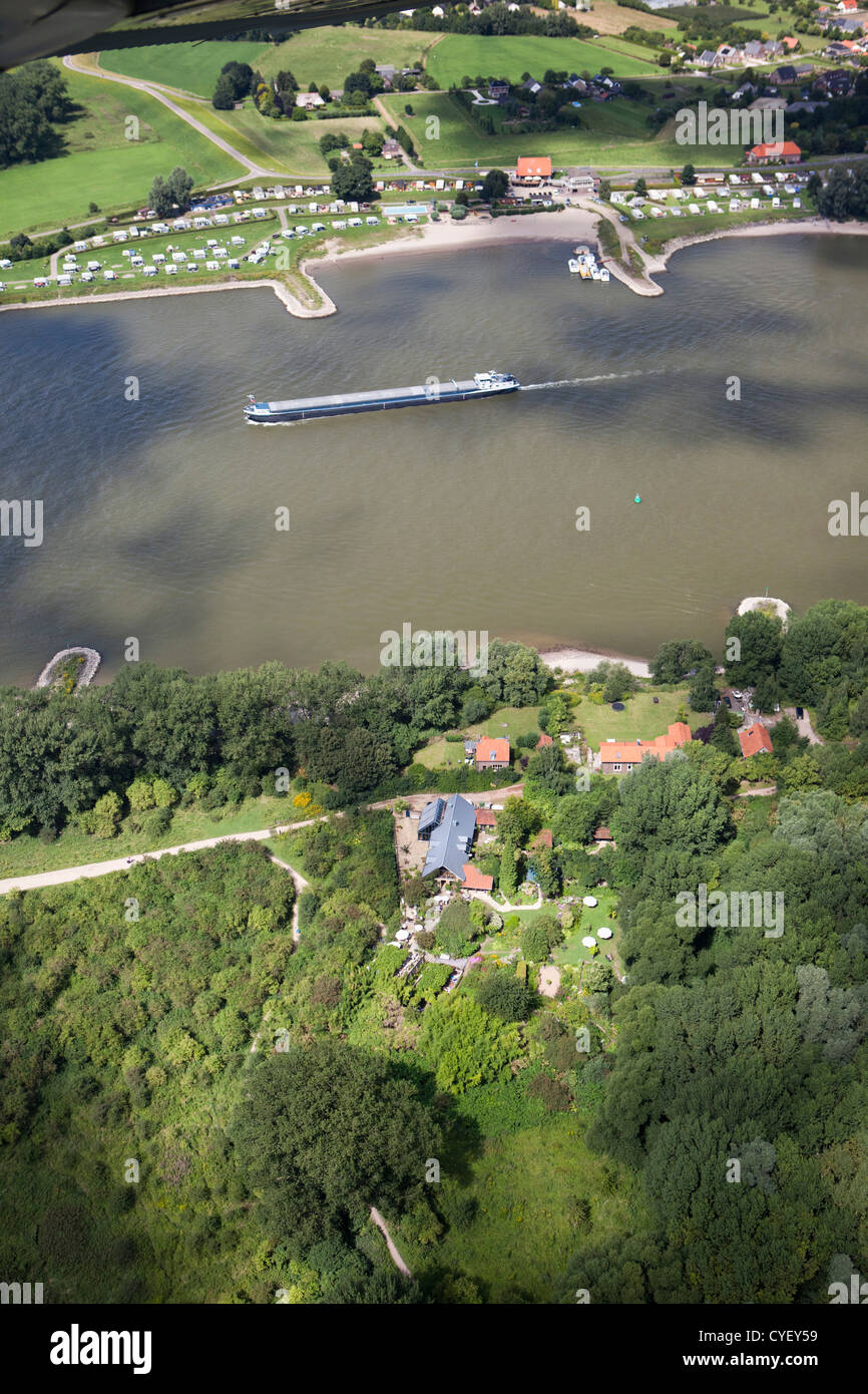 Cargo boat in Waal river. Foreground tea garden called Millinger Theetuin. Opposite campsite. Aerial. - Stock Image