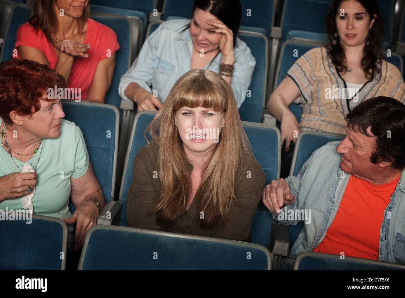 Weeping woman and distracted people in the audience - Stock Image