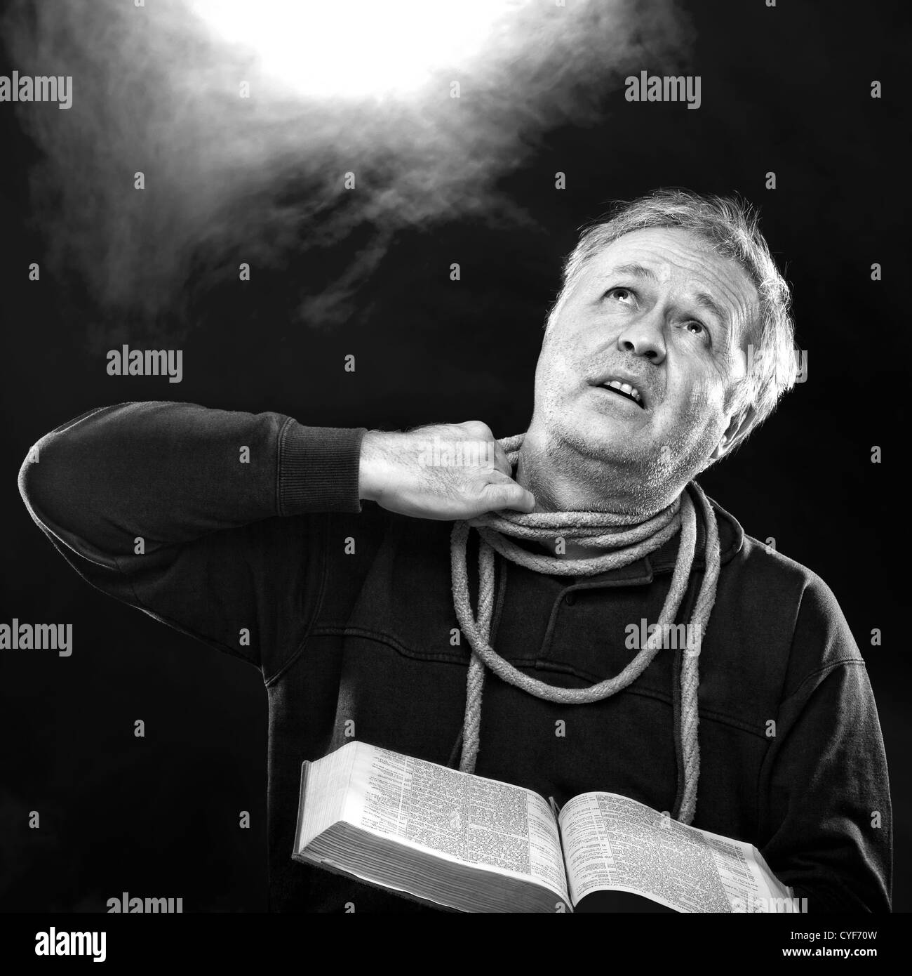 Man with Bible trying to untie rope from neck: O Jerusalem: loose thyself from the bands of thy neck, O captive - Stock Image
