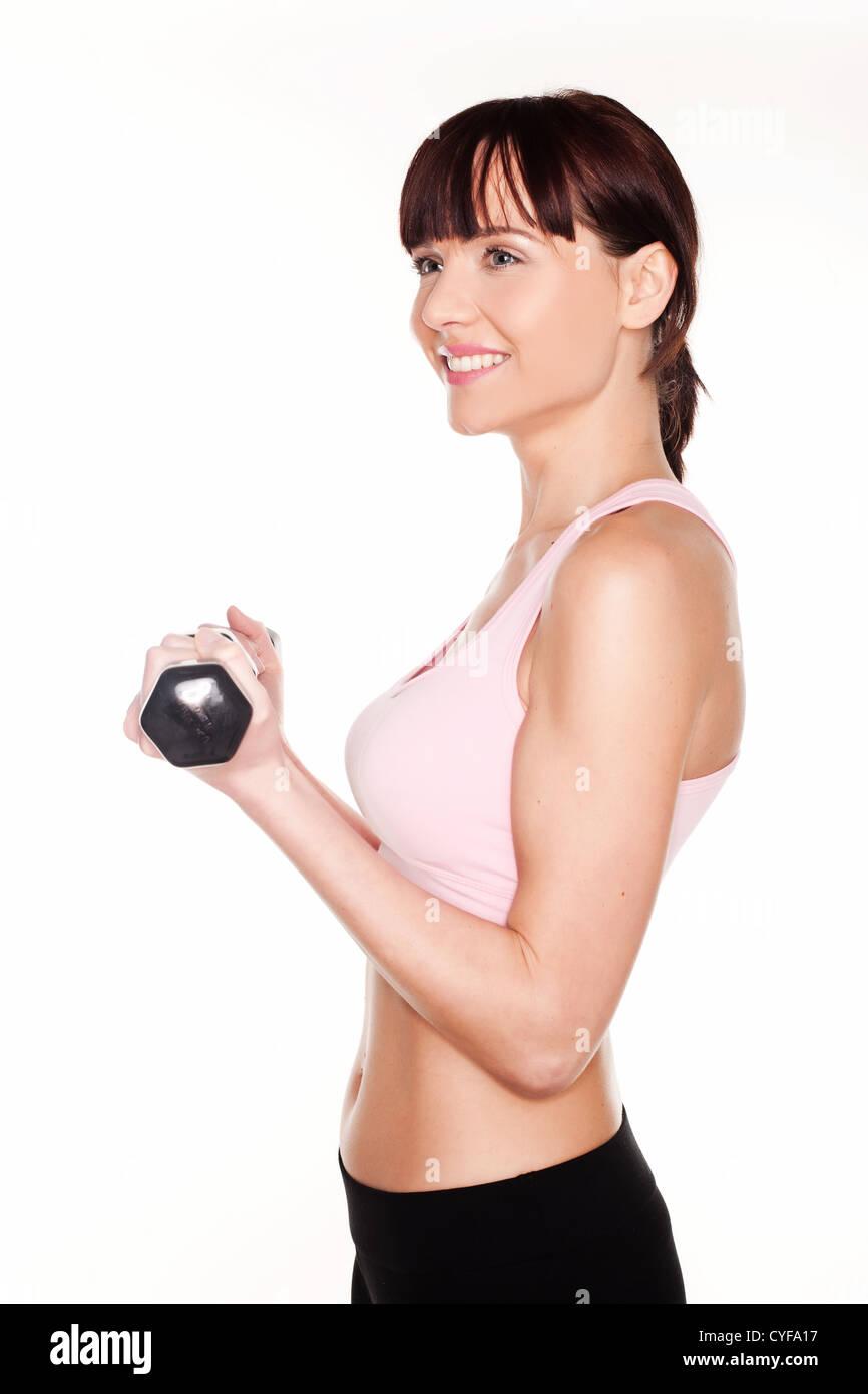 Upper body profile of a young woman flexing a raising her arm while holding a dumbbell isolated on white - Stock Image