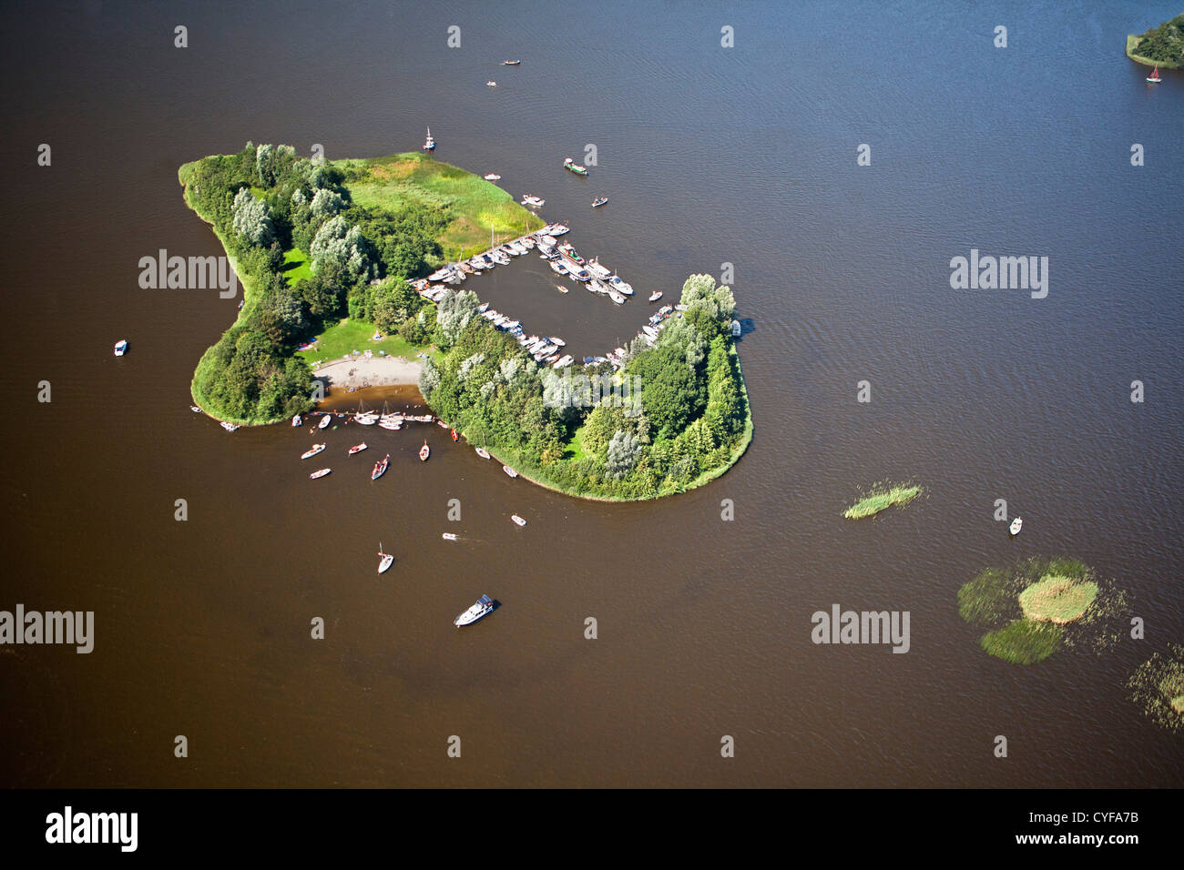 The Netherlands, Loosdrecht, Sailing boats and motor yachts anchored near island in Loosdrecht Lakes. Aerial. - Stock Image