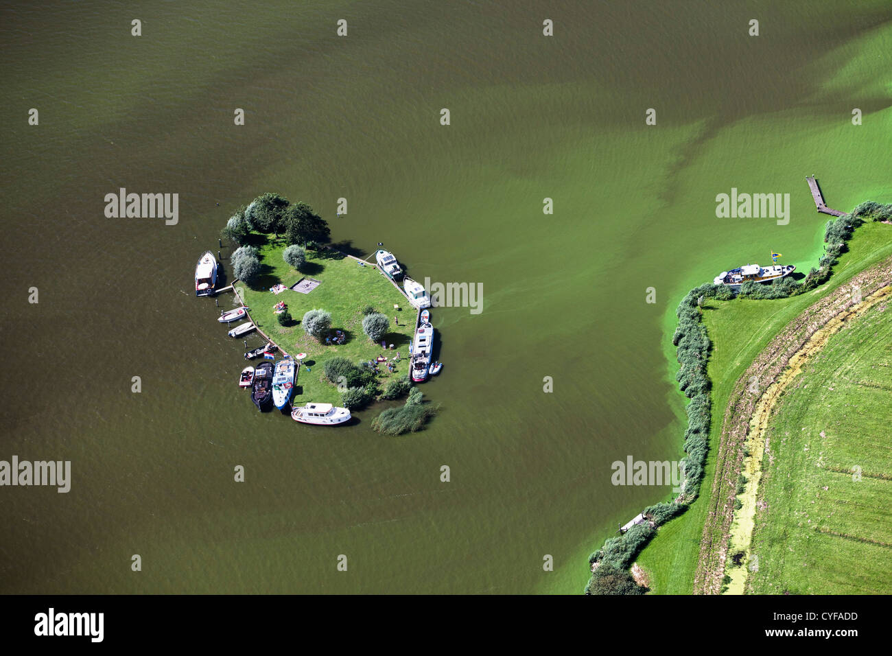 The Netherlands, Akersloot, lake called Alkmaardermeer. Yachts anchored near island. Aerial. - Stock Image