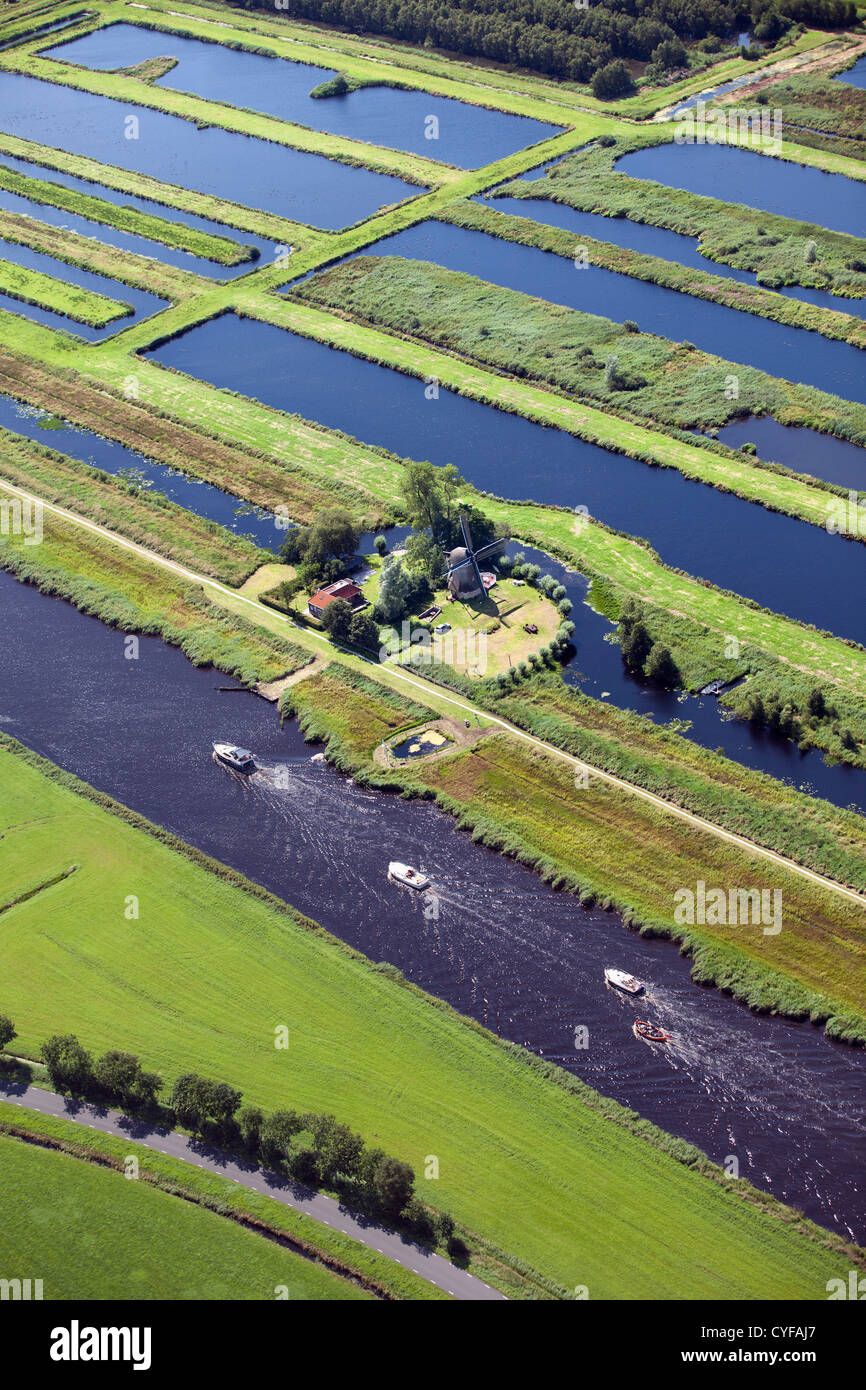Village with many canals and lakes due to digging peat. Most transport is by waterways. Windmill. Aerial. - Stock Image