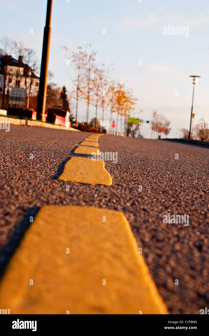 Yellow dividing line on asphalt road - Stock Image