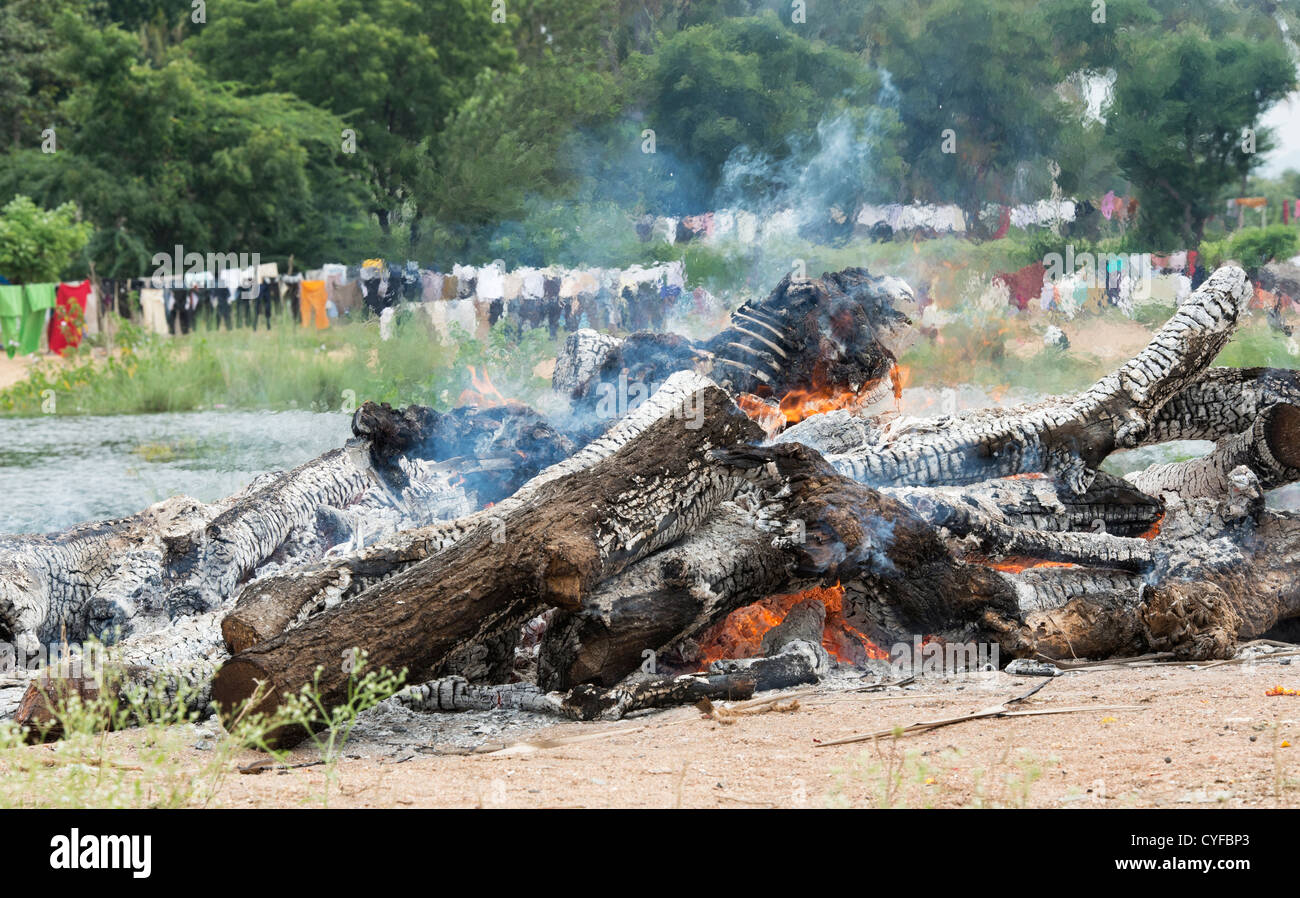 Cremating a human body on a hindu funeral pyre nesxt to a river. Andhra pradesh, India - Stock Image