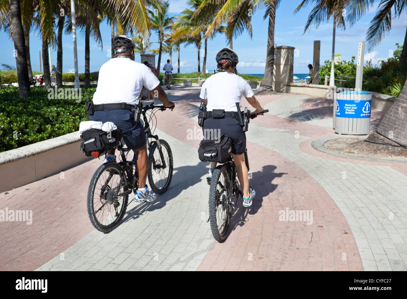 Rear view of two police officers on bicycle patrol along promenade, Miami Beach, Florida, USA. - Stock Image