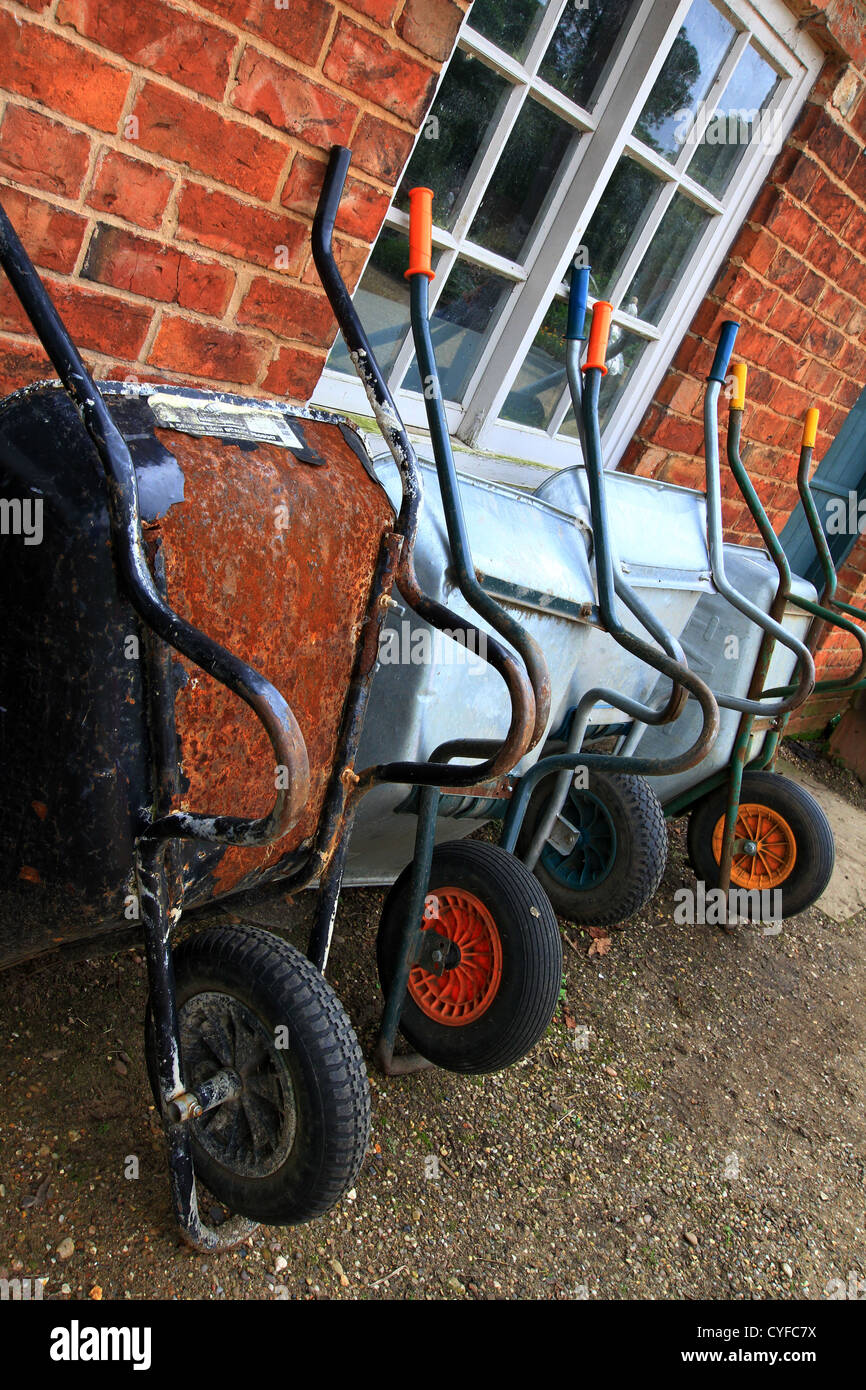 Four wheelbarrows, a rusty old one and 3 x new ready for action. Usually found in Gardens or building sites.A handy - Stock Image