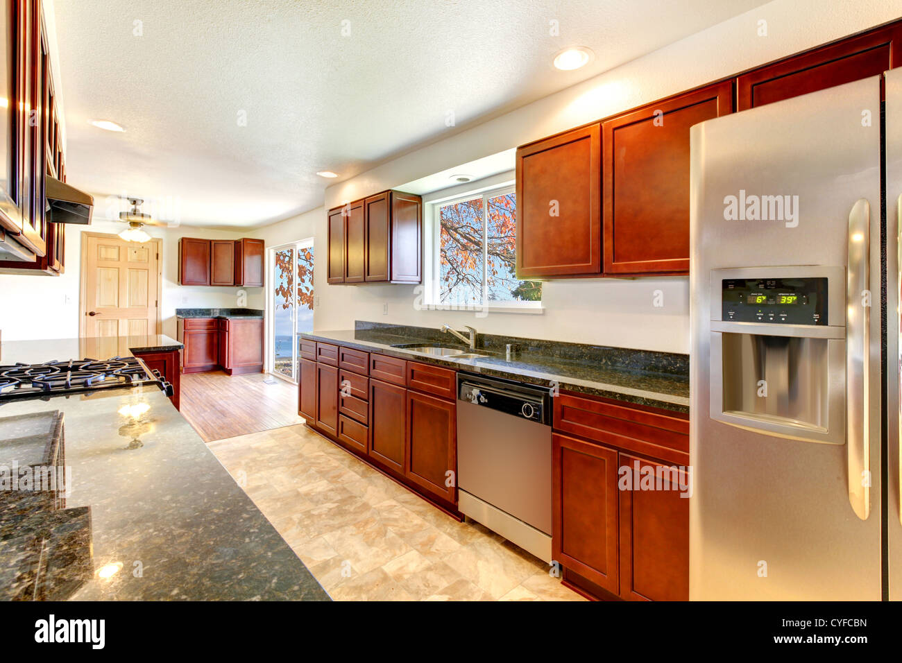 Large Bright Kitchen With Dark Cherry Cabinets And Stainless