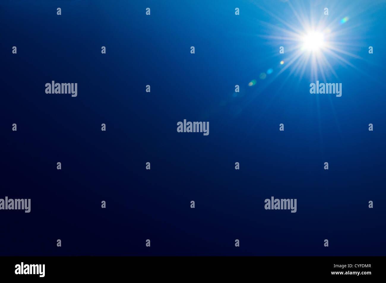 Bright sun on a deep blue sky background - Stock Image