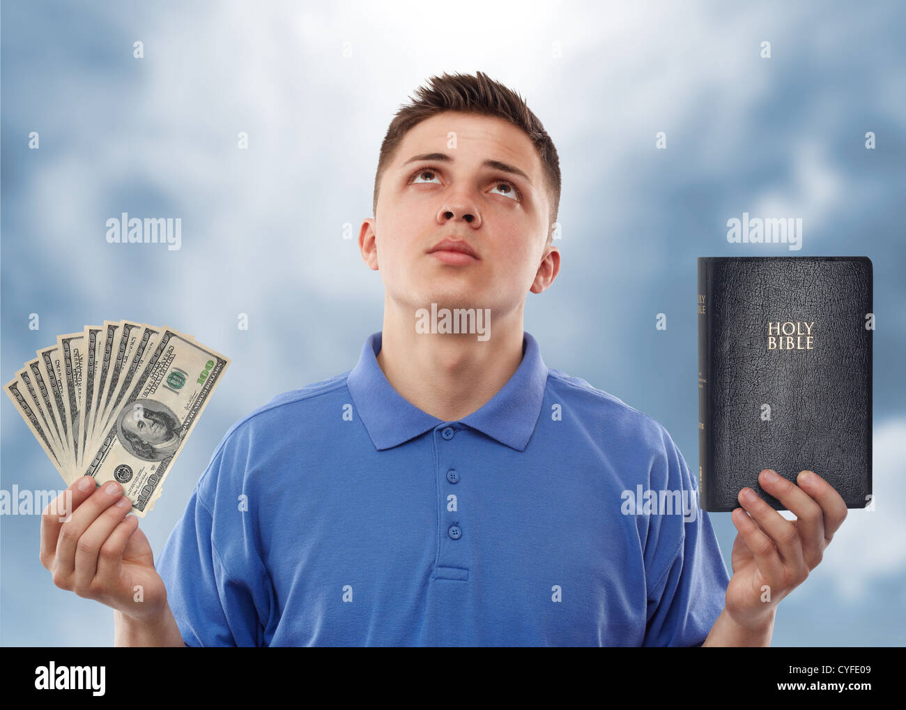 Young man asking for help to choose between God and money. 'No man is able to be a servant to two masters.' - Stock Image