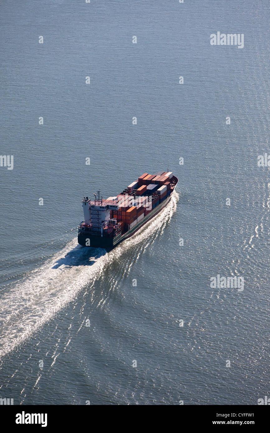 The Netherlands, Nieuw Namen. Container ship in Westerschelde river. Aerial. - Stock Image