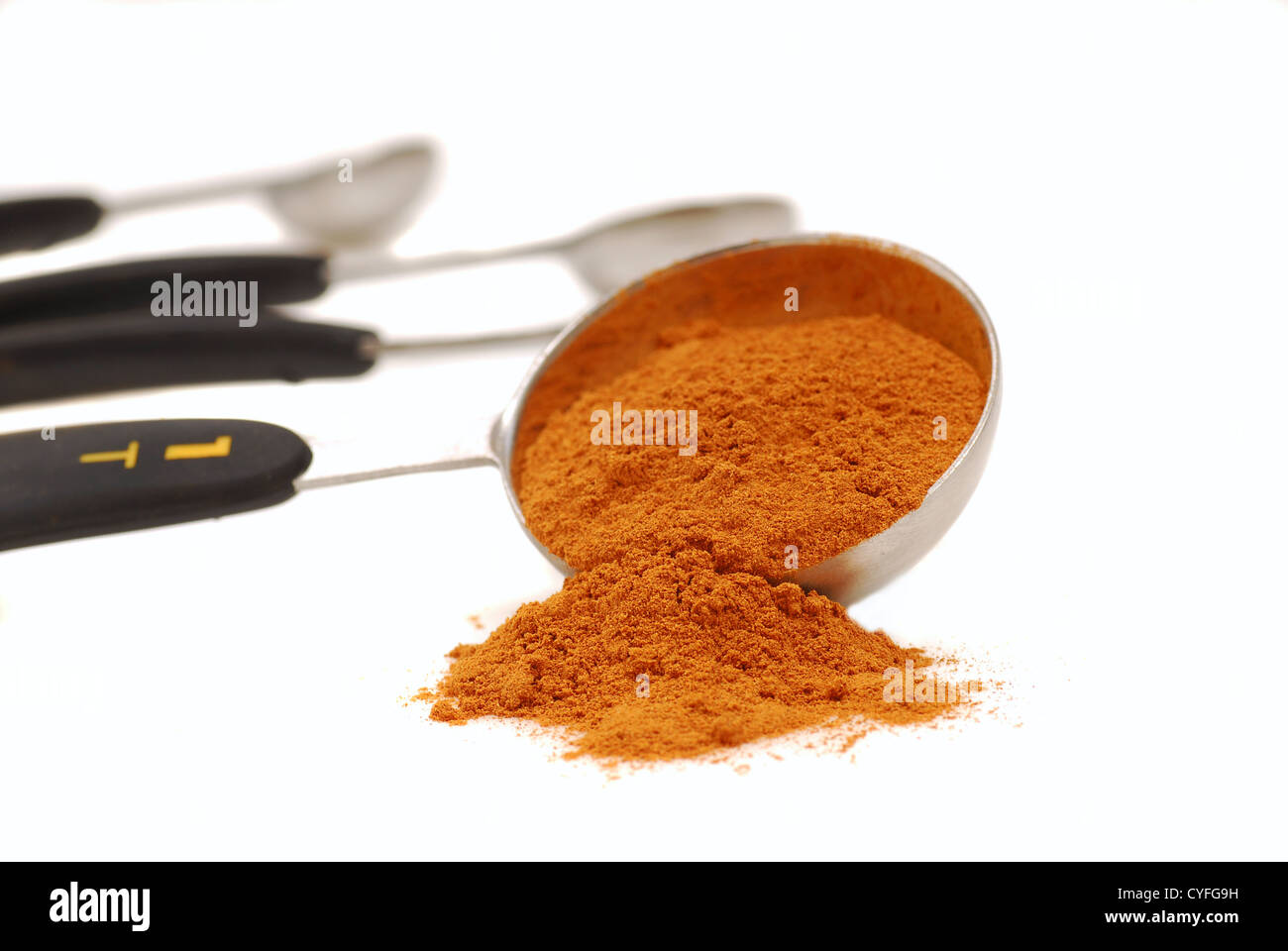 Freshly ground cinnamon spilling out of a measuring spoon. - Stock Image