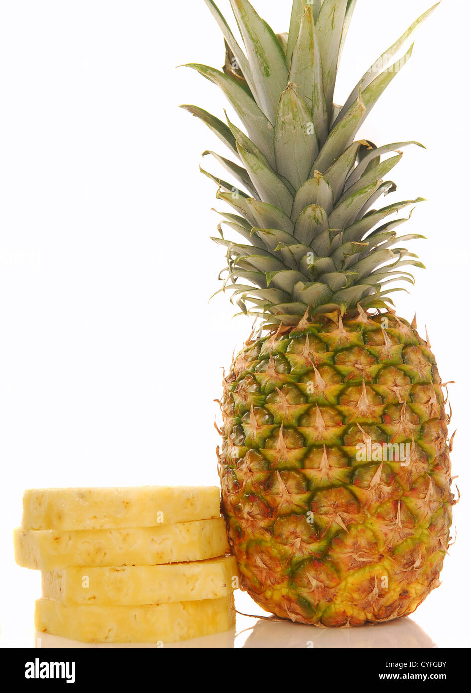 Fresh whole tropical pineapple with several slices stacked next to it on a white background - Stock Image