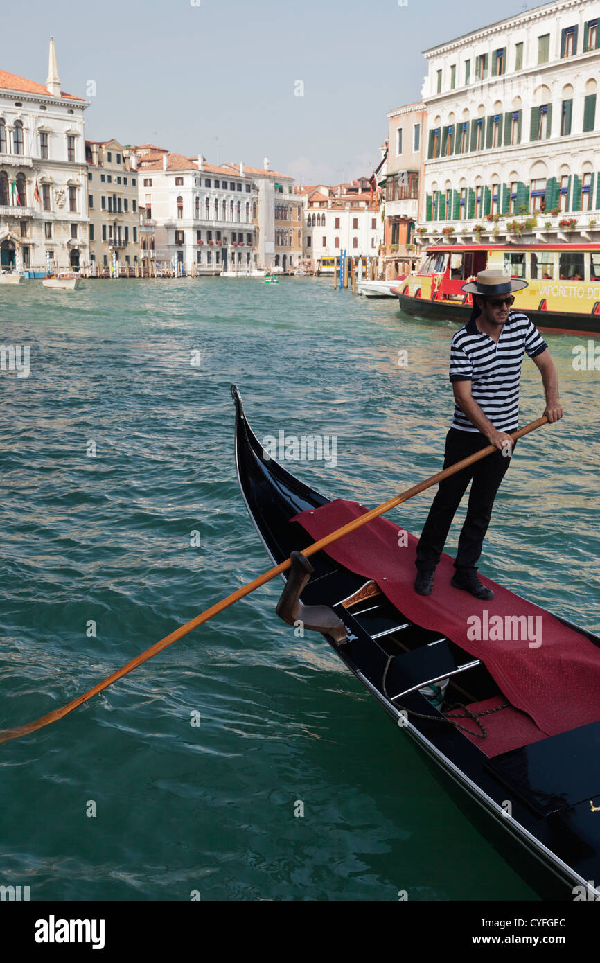 7b40405c7ef Gondolier on the Grand Canal in Venice wearing traditional stripped shirt  and straw boater hat -