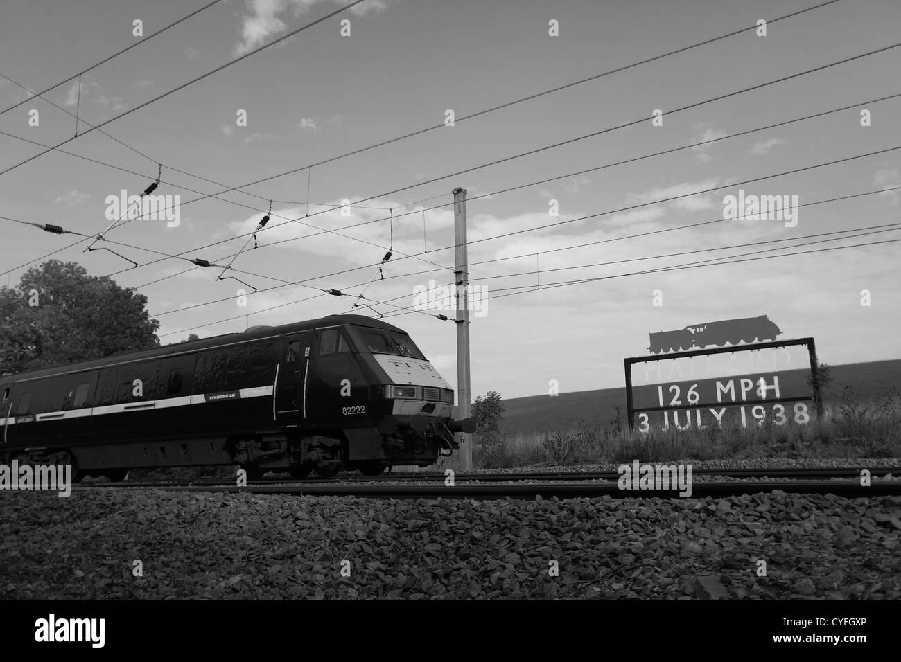 East Coast train 82222 DVT Electric Train passing the Mallard Speed Record Sign Carlby village East Coast Main Line - Stock Image