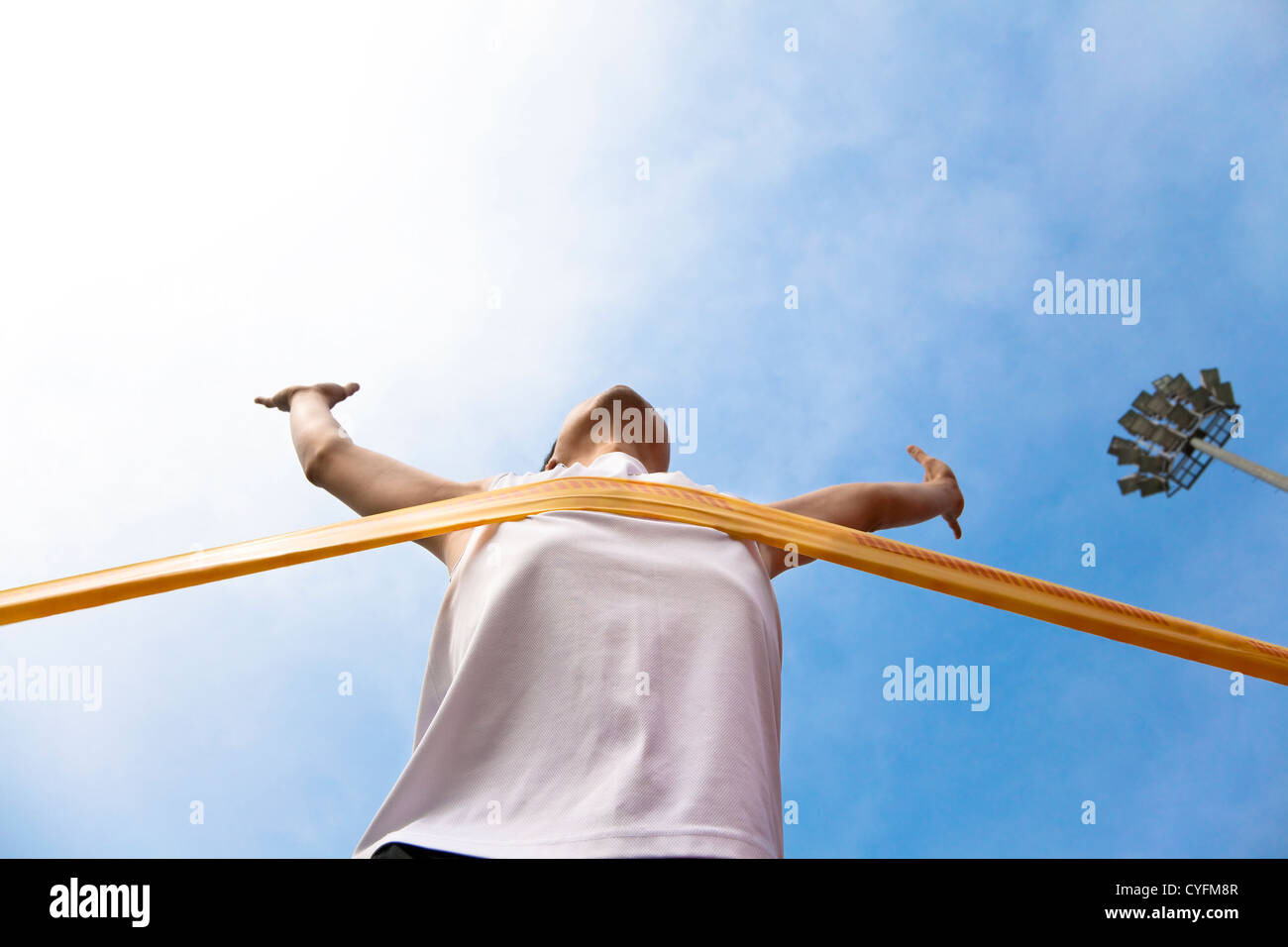 Winning athlete with cloud background - Stock Image