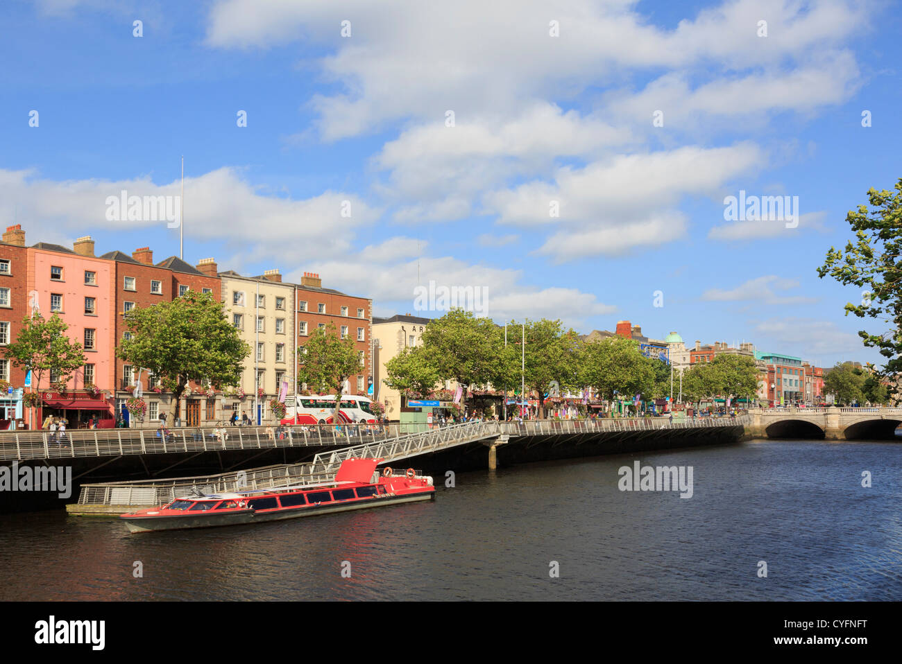 View across the River Liffey to Batchelor's Walk with cruise boat moored by jetty from Temple Bar, Dublin, Ireland, - Stock Image