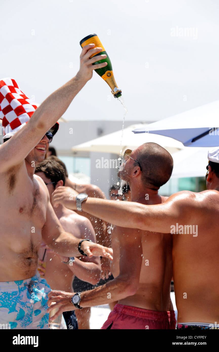 British party goers pouring bottles of champagne over each other at beach club - Stock Image