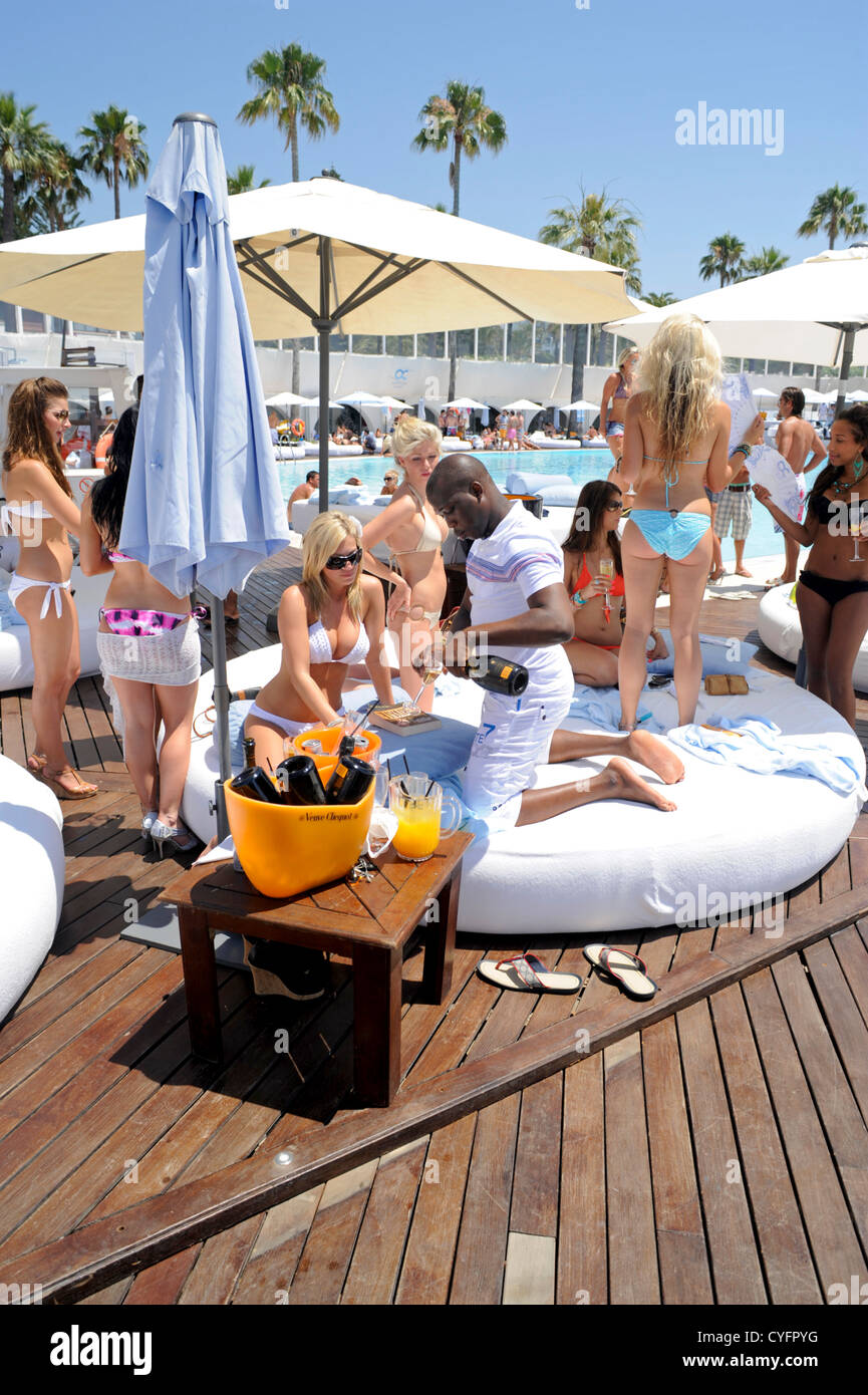 Party goers on large round sun lounger drinking champagne - Stock Image