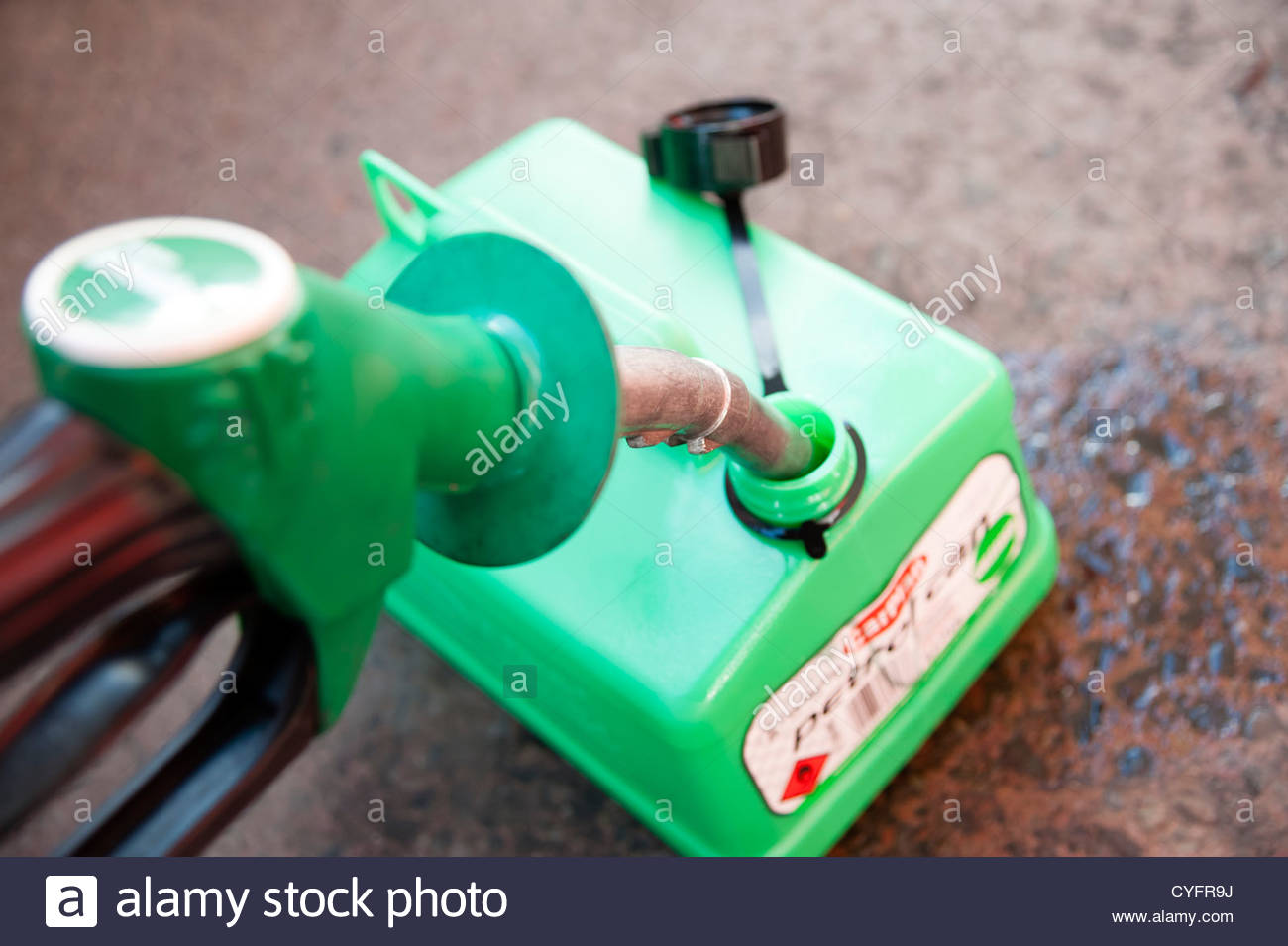 Filling up a petrol can with unleaded fuel, UK. Close up of a petrol pump nozzle in fuel can on the garage forecourt. - Stock Image