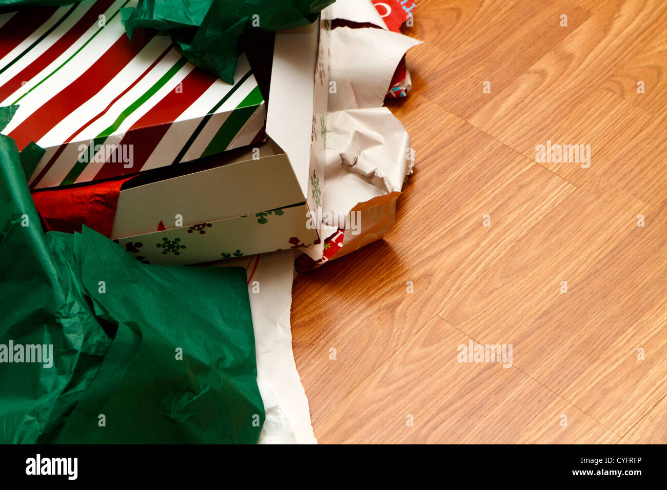A pile of unwrapped gift boxes and ripped wrapping paper on the floor at Christmas time. Copy space was left on - Stock Image