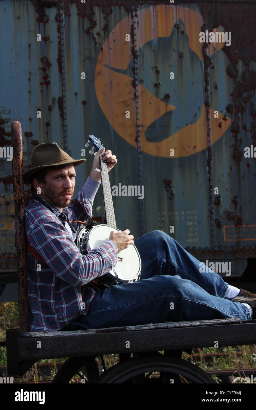 Male model as a hobo playing banjo while sitting on an old railroad baggage cart. - Stock Image