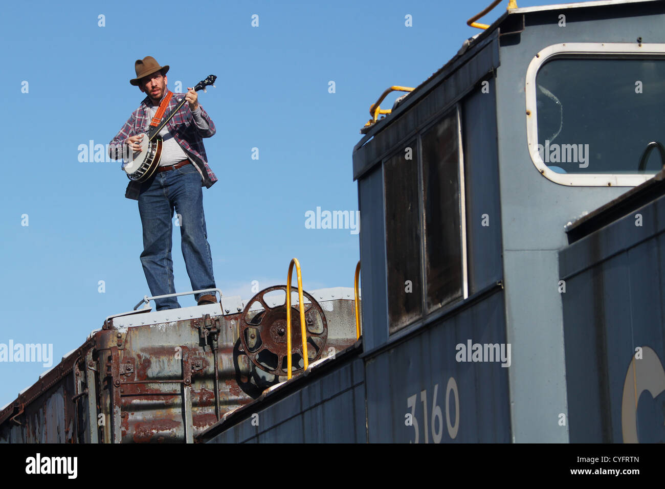 Male model as a hobo playing banjo while standing on a railroad box car. - Stock Image