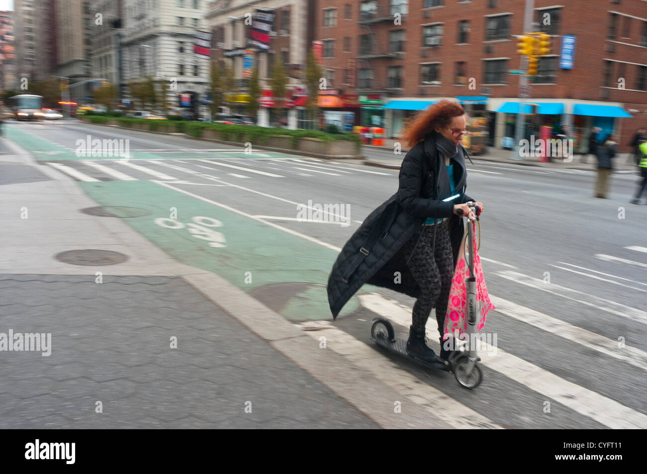 New York, NY -  2 November 2012 Woman on a kick scooter carrying groceries and other provisions through Lower Manhattan - Stock Image